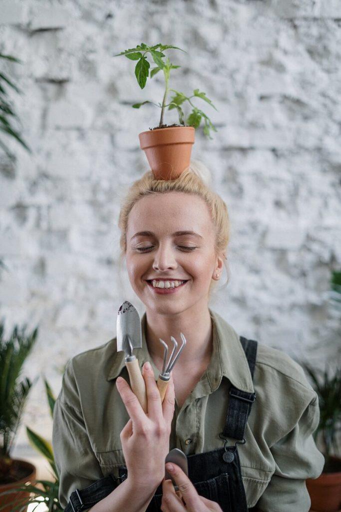 personne avec un pot de fleur sur la tête